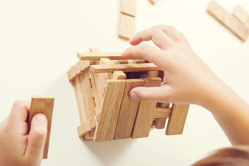 Πρότυπη κατασκευή σπιτιών Το παιδί χτίζει το μικρό ξύλινο σπίτι, κινηματογράφηση σε πρώτο πλάνο Όνειρο για το νέο σπίτι Επιχειρησ στοκ φωτογραφία