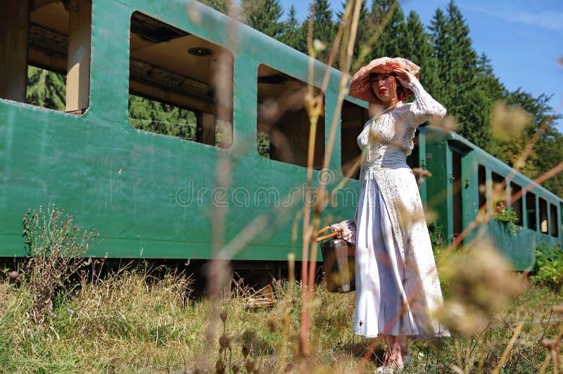 Πρότυπη κυρία κοντά σε ένα εκλεκτής ποιότητας τραίνο στοκ εικόνα