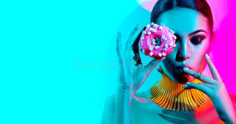 Πρότυπη τοποθέτηση γυναικών μόδας στο στούντιο με doughnut στοκ εικόνα