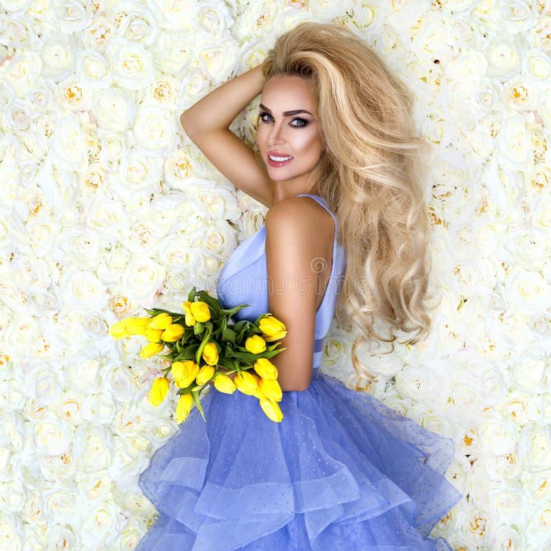 Πρότυπο γαμήλιων φορεμάτων μόδας με μια ανθοδέσμη των τουλιπών Όμορφο πρότυπο νυφών στο μπλε καταπληκτικό γαμήλιο φόρεμα Νέα γυνα στοκ εικόνες