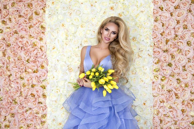 Πρότυπο γαμήλιων φορεμάτων μόδας με μια ανθοδέσμη των τουλιπών Όμορφο πρότυπο νυφών στο μπλε καταπληκτικό γαμήλιο φόρεμα Νέα γυνα στοκ φωτογραφία
