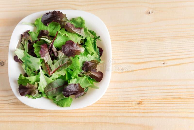 Πρότυπο για ένα έμβλημα με ένα πιάτο της πράσινης σαλάτας σε ένα ξύλινΠστοκ φωτογραφίες