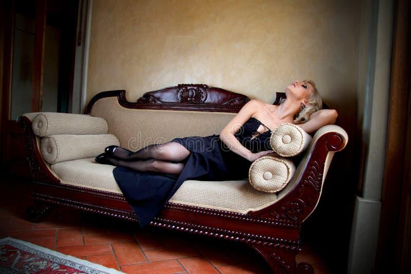 Πρότυπο γοητείας με το μαύρο φόρεμα βραδιού που βρίσκεται σε έναν σύγχρονο βικτοριανό καναπέ στοκ εικόνες