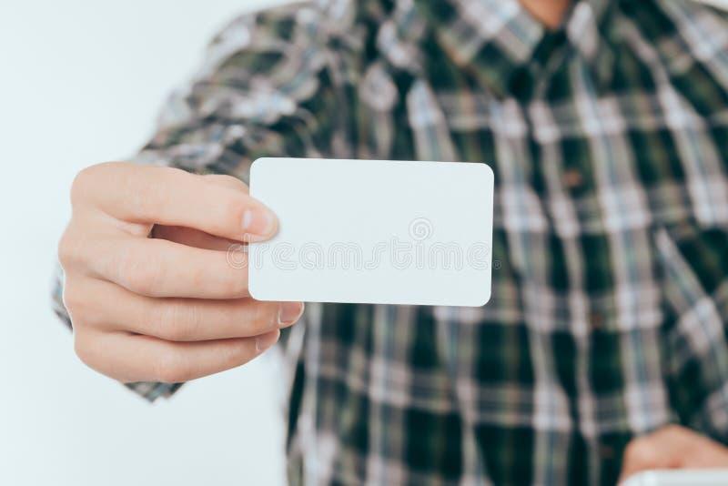 Πρότυπο επαγγελματικών καρτών: Ο νεαρός άνδρας που παρουσιάζει ή που δίνει κενή επαγγελματική κάρτα μας χρησιμοποιεί για τη χλεύη στοκ εικόνα