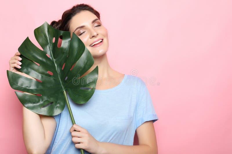Πρότυπο εφήβων με τα πράσινα φύλλα πέρα από το ρόδινο backfround στοκ φωτογραφία