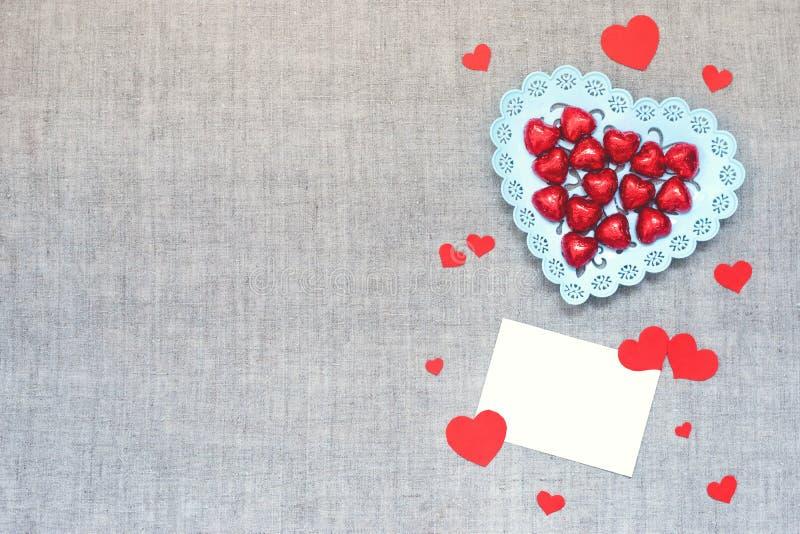Πρότυπο ημέρας βαλεντίνων με τις καραμέλες σοκολάτας καρδιών στο πιάτο, πολλές καρδιές εγγράφου και κενή κάρτα στο υπόβαθρο υφάσμ στοκ φωτογραφία με δικαίωμα ελεύθερης χρήσης