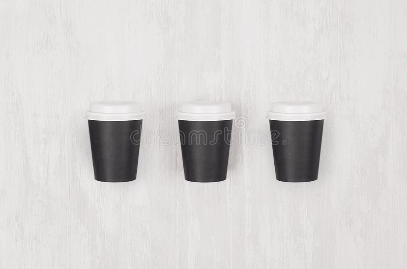 Πρότυπο καφέ - σύνολο τριών μικρών κενών μαύρων φλυτζανιών εγγράφου με τα άσπρα καλύμματα στο λευκό ξύλινο πίνακα, τοπ άποψη στοκ εικόνα