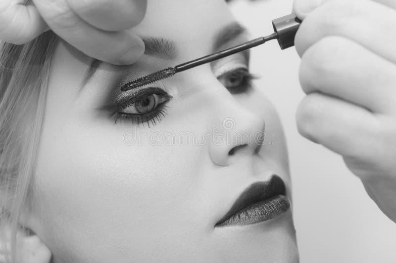 Πρότυπο κορίτσι μόδας που παίρνει mascara στα eyelashes στοκ φωτογραφία