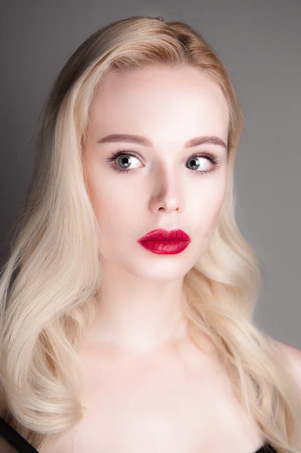 Πρότυπο κορίτσι ομορφιάς με τα τέλεια κόκκινα χείλια και τα μπλε μάτια σύνθεσης που εξετάζει τη κάμερα Πορτρέτο της ελκυστικής νέ στοκ φωτογραφία