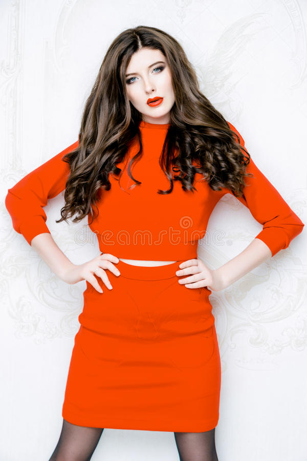 Πρότυπο με το μακρυμάλλες φορώντας κόκκινο φόρεμα με τις μπούκλες Hairstyle κυμάτων στοκ φωτογραφίες με δικαίωμα ελεύθερης χρήσης