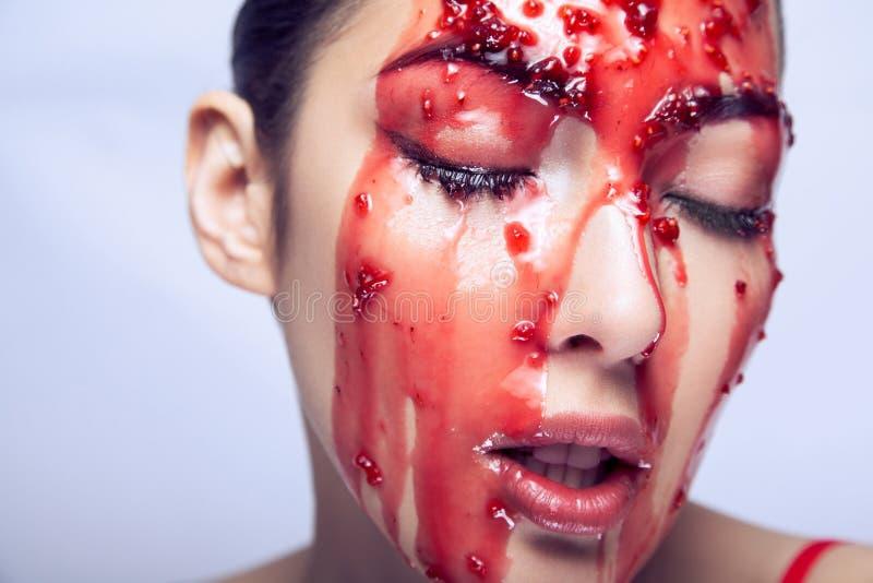 Πρότυπο μόδας που επιδεικνύει πώς η μαρμελάδα ρέει πέρα από το μάγουλό της και απολαμβάνει στοκ φωτογραφίες με δικαίωμα ελεύθερης χρήσης