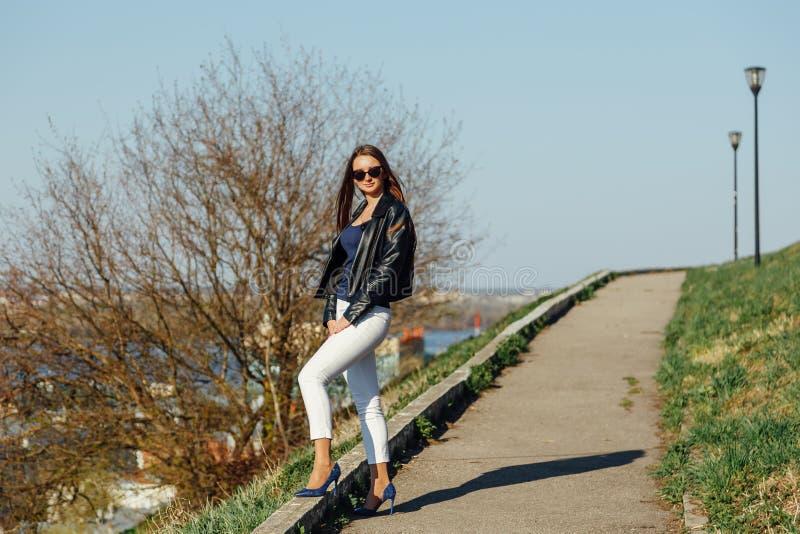 Πρότυπο μόδας στα γυαλιά ηλίου και τη μαύρη τοποθέτηση σακακιών δέρματος υπαίθρια στοκ φωτογραφία