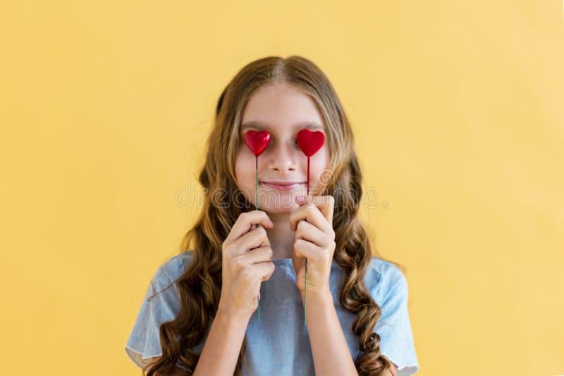 Πρότυπο νέων κοριτσιών με την καρδιά του βαλεντίνου στα χέρια της Έννοια της αγάπης Δώρο ημέρας βαλεντίνων ` s Στο κίτρινο υπόβαθ στοκ εικόνα με δικαίωμα ελεύθερης χρήσης