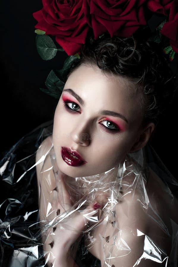 Πρότυπο πρόσωπο γυναικών μόδας ομορφιάς Πορτρέτο με τα κόκκινα ροδαλά λουλούδια Κόκκινα χείλια και καρφιά Όμορφη γυναίκα Brunette στοκ εικόνες