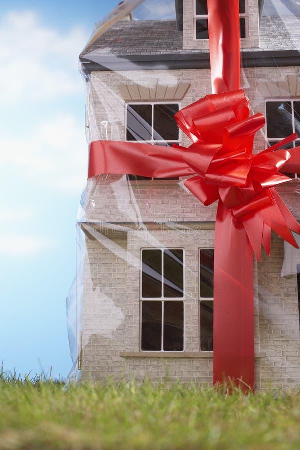 Πρότυπο σπίτι δώρο-που τυλίγεται με την κόκκινη κινηματογράφηση σε πρώτο πλάνο κορδελλών και τόξων στοκ εικόνα
