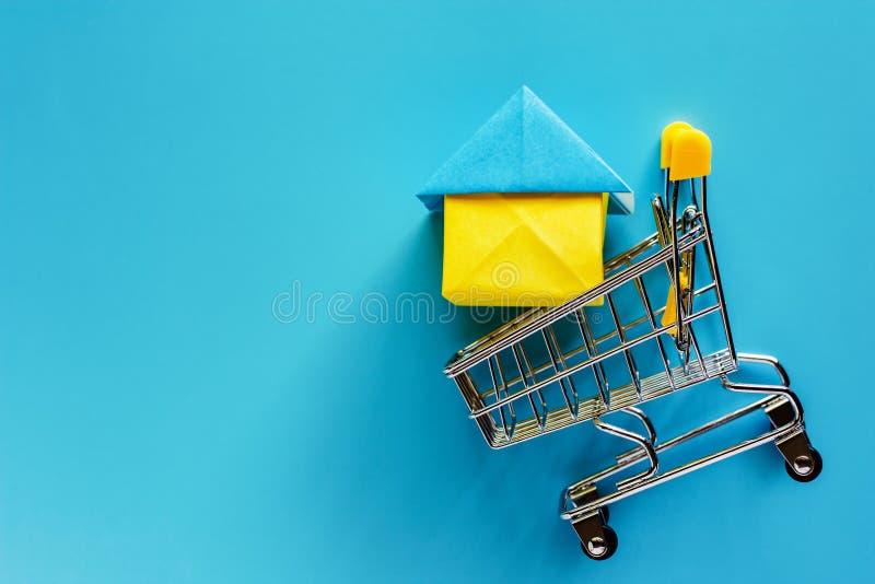 Πρότυπο σπιτιών εγγράφου στο μίνι κάρρο αγορών ή καροτσάκι στο μπλε backg στοκ εικόνα