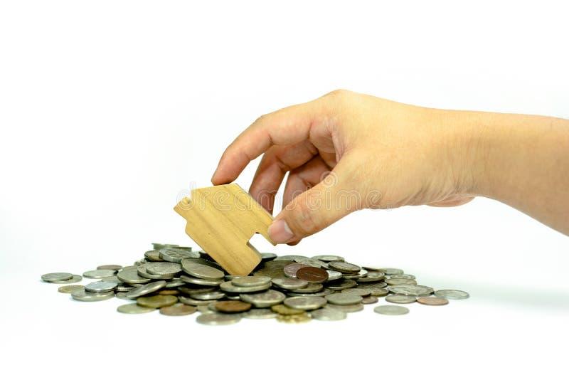 Πρότυπο σπιτιών εκμετάλλευσης χεριών στην αποταμίευση σωρών νομισμάτων για την έννοια με απομονωμένος στο άσπρο υπόβαθρο Έννοια γ στοκ εικόνες