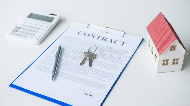 Πρότυπο σπιτιών, υπολογιστής και κλειδί σπιτιών που βρίσκεται στη σύμβαση ακίνητων περιουσιών, το στεγαστικό δάνειο και την έννοι στοκ εικόνα