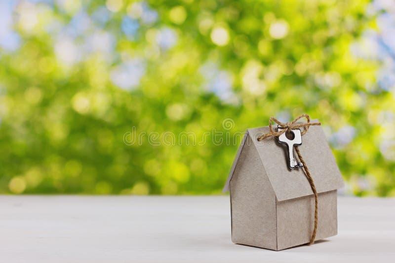 Πρότυπο του σπιτιού χαρτονιού με ένα τόξο του σπάγγου και του κλειδιού στο πράσινο κλίμα bokeh στοκ φωτογραφία