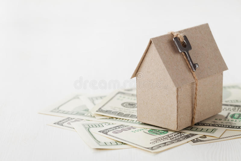 Πρότυπο του σπιτιού χαρτονιού με τους λογαριασμούς κλειδιών και δολαρίων Οικοδόμηση, δάνειο, ακίνητη περιουσία, κόστος ή ένα νέο  στοκ εικόνα