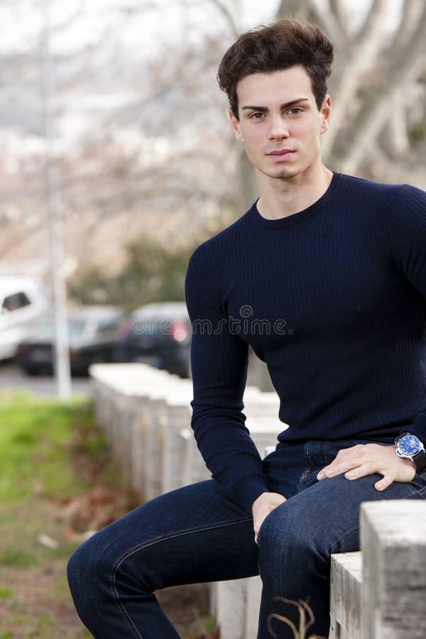Πρότυπο υπαίθριο άτομο, που κάθεται σε έναν χαμηλό τοίχο στην πόλη στοκ φωτογραφία
