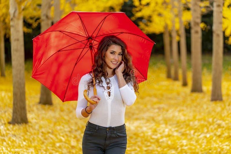 Πρότυπο Brunette που απολαμβάνει μια ημέρα πτώσης στο φύλλωμα πτώσης με μια κόκκινη ομπρέλα στοκ φωτογραφία