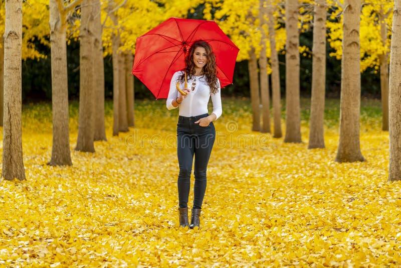 Πρότυπο Brunette που απολαμβάνει μια ημέρα πτώσης στο φύλλωμα πτώσης με μια κόκκινη ομπρέλα στοκ φωτογραφία με δικαίωμα ελεύθερης χρήσης