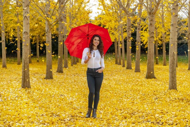 Πρότυπο Brunette που απολαμβάνει μια ημέρα πτώσης στο φύλλωμα πτώσης με μια κόκκινη ομπρέλα στοκ εικόνα