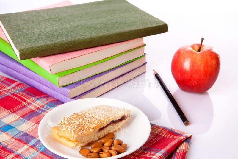 Πρόχειρα φαγητά, μήλο και βιβλία στοκ φωτογραφία