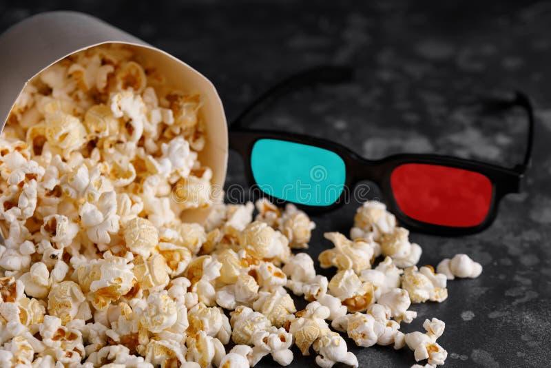 Πρόχειρο φαγητό για τους κινηματογράφους προσοχής Ένας κάδος popcorn σε ένα σκοτεινό υπόβαθρο και τρισδιάστατα γυαλιά στοκ εικόνες