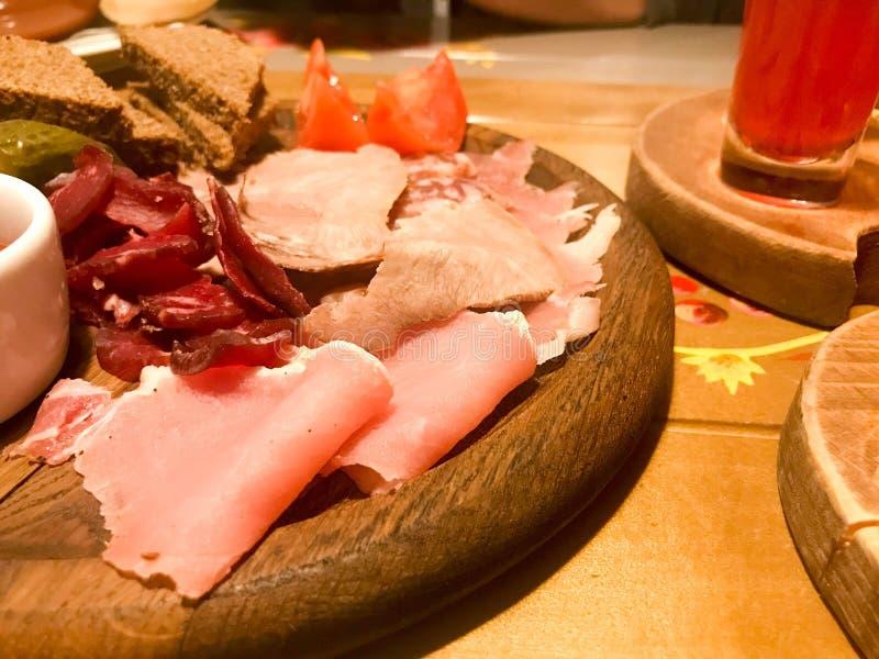Πρόχειρο φαγητό κρέατος με το οινόπνευμα από το κρέας, ζαμπόν, basturma με τη σάλτσα στις ξύλινες στάσεις στον πίνακα σε έναν καφ στοκ φωτογραφίες