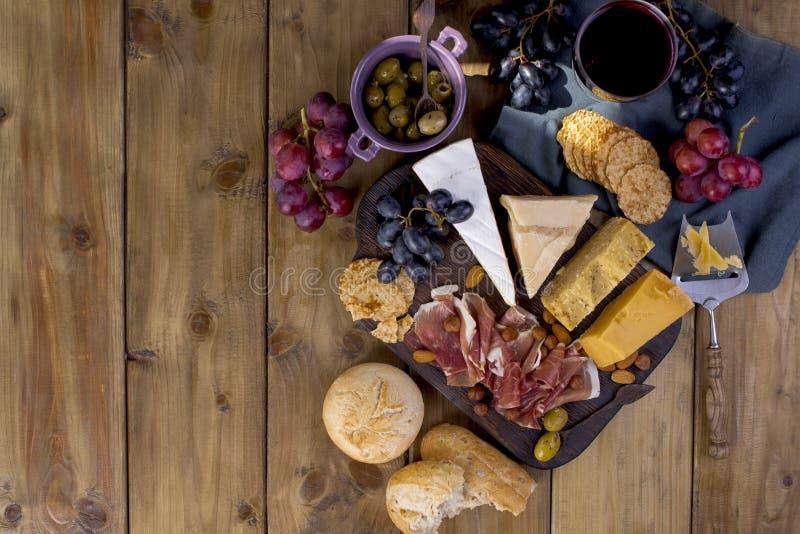 Πρόχειρο φαγητό στο κρασί Ζαμπόν, διαφορετικό τυρί, ελιές, σταφύλια, ψωμί και κόκκινο κρασί σε ένα γυαλί Ξύλινη ανασκόπηση μαγειρ στοκ εικόνες