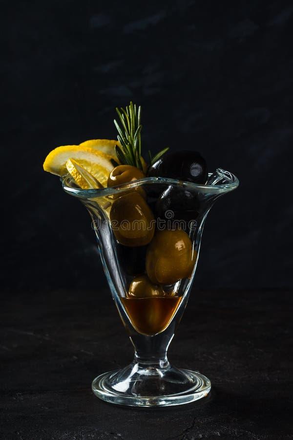 Πρόχειρο φαγητό των πράσινων και μαύρων ελιών, λεμόνι με ένα κλαδάκι του δεντρολιβάνου στοκ εικόνες με δικαίωμα ελεύθερης χρήσης