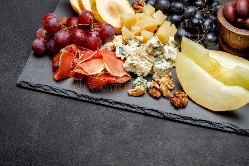 Πρόχειρο φαγητό antipasti πιάτων κρέατος - ζαμπόν Prosciutto, μπλε τυρί, πεπόνι, σταφύλια, ελιές στοκ εικόνες