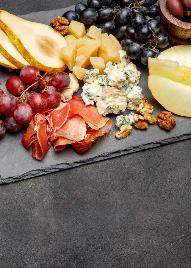Πρόχειρο φαγητό antipasti πιάτων κρέατος - ζαμπόν Prosciutto, μπλε τυρί, πεπόνι, σταφύλια, ελιές στοκ εικόνα