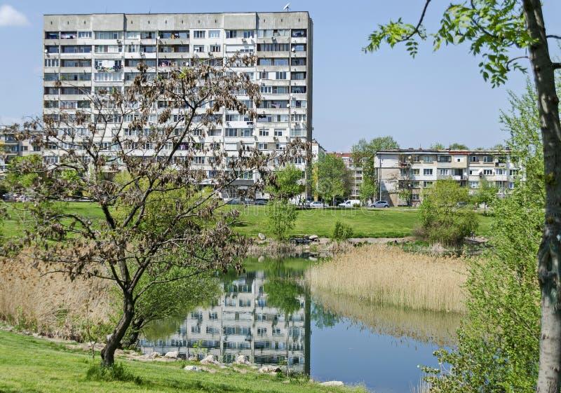 Πρόωρος πράσινος, ξηρός κάλαμος άνοιξης ή βιασύνη και σπίτι σε μια λίμνη ομορφιάς στην κατοικημένη περιοχή Drujba στοκ φωτογραφίες