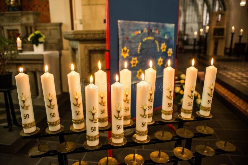 Πρώτα ιερά καίγοντας κεριά κοινωνίας ή επιβεβαίωσης που κωπηλατούνται επάνω στην εκκλησία πριν από την όμορφη διακόσμηση τελετής στοκ φωτογραφία με δικαίωμα ελεύθερης χρήσης
