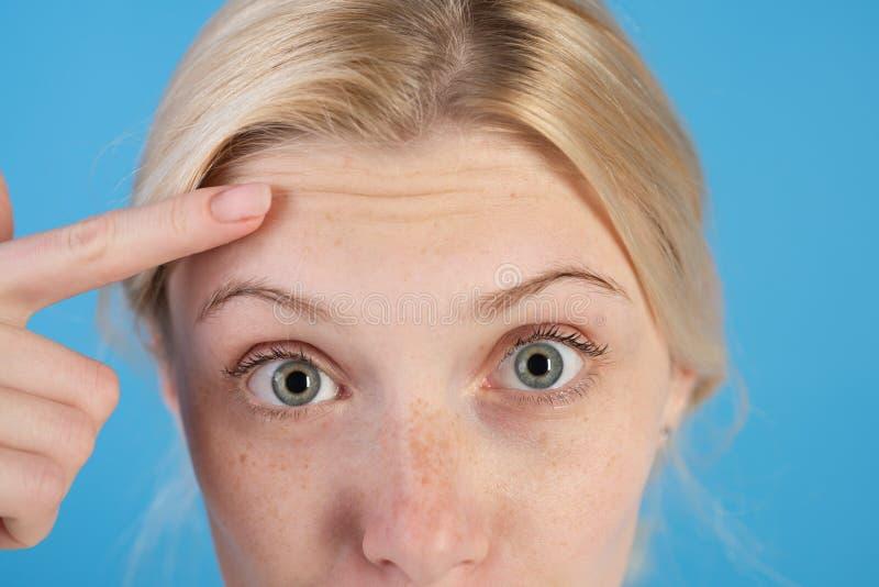 Πρώτες ρυτίδες Να αναρωτηθεί γυναικών το πρόσωπο παρουσιάζει ρυτίδες στο μέτωπο o Αντι κρέμα δερμάτων ηλικίας Καλλυντικά και στοκ φωτογραφίες με δικαίωμα ελεύθερης χρήσης
