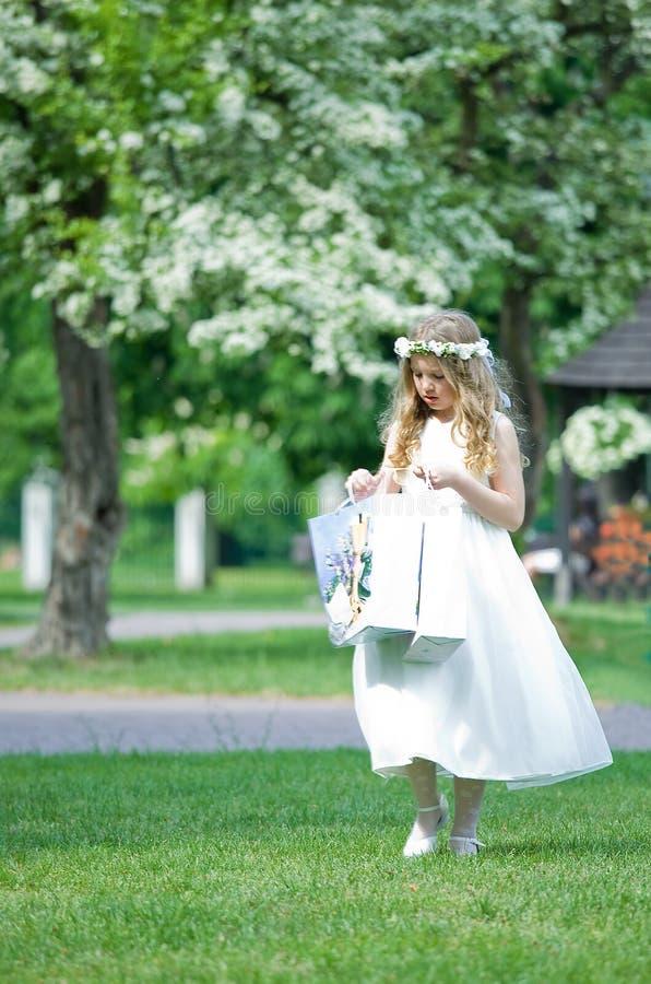 Πρώτη κοινωνία - το κορίτσι εξετάζει τα δώρα της στοκ εικόνα