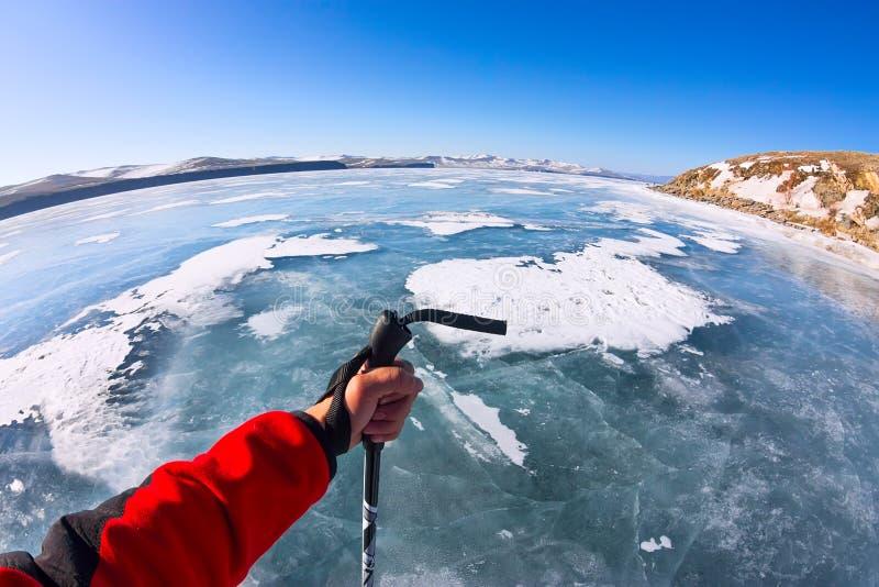 Πρώτο ραβδί gopro άποψης προσώπων στο χέρι του στον πάγο της λίμνης Bai στοκ εικόνα με δικαίωμα ελεύθερης χρήσης