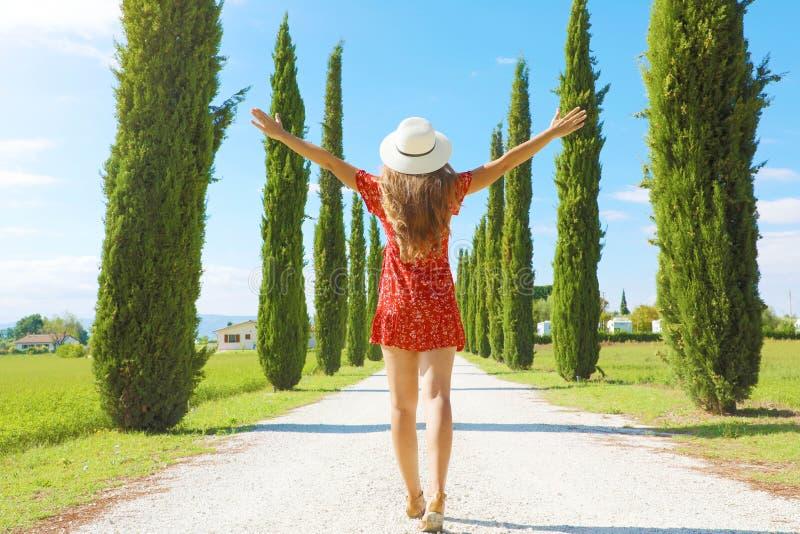 Πτήση στην Τοσκάνη Νεαρή γυναίκα περπατάει σε όμορφα και ειδυλλιακά τοπία μιας λωρίδας κυπαρίσσας στα ιταλικά στοκ φωτογραφίες