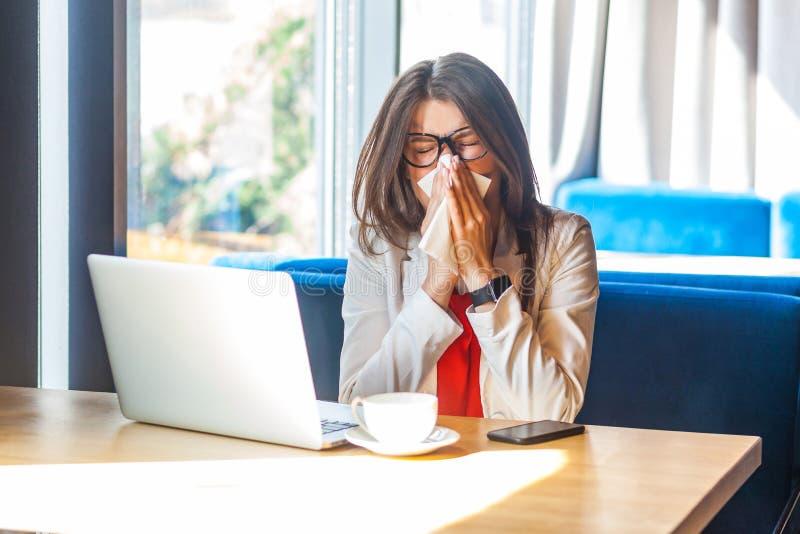 Πταρμός, κρυολόγημα, γρίπη ή αλλεργίες Πορτραίτο της αρρωστημένης κομψής μελαχρινής νεαρής γυναίκας με γυαλιά που κάθεται κρατώντ στοκ φωτογραφία με δικαίωμα ελεύθερης χρήσης