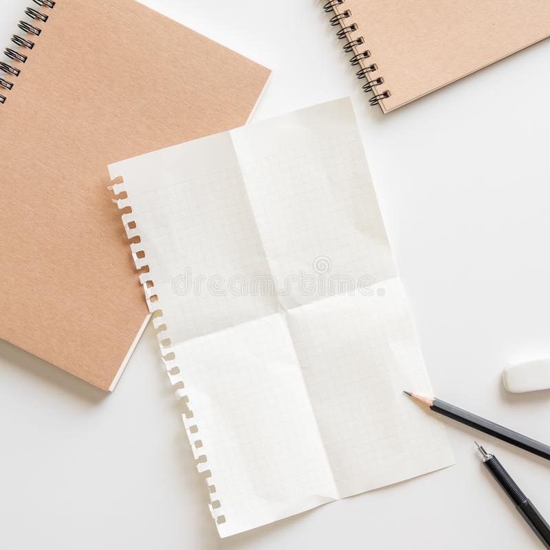 Πτυχές εγγράφου γραφικών παραστάσεων με το σπειροειδείς σημειωματάριο, το μολύβι και τη γόμα στο μόριο στοκ φωτογραφία με δικαίωμα ελεύθερης χρήσης