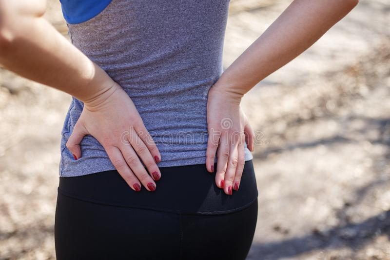 πτυχίου Γυναίκα σχετικά με μικρό της πίσω Overlo σπονδυλικών στηλών στοκ εικόνα με δικαίωμα ελεύθερης χρήσης