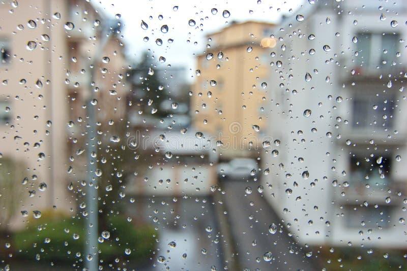 Πτώσεις βροχής κινηματογραφήσεων σε πρώτο πλάνο σε ένα παράθυρο στοκ εικόνες