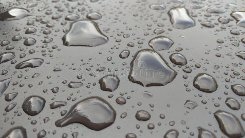 Πτώσεις της πτώσης βροχής ή νερού στην κουκούλα του αυτοκινήτου Πτώσεις ο βροχής στοκ φωτογραφία