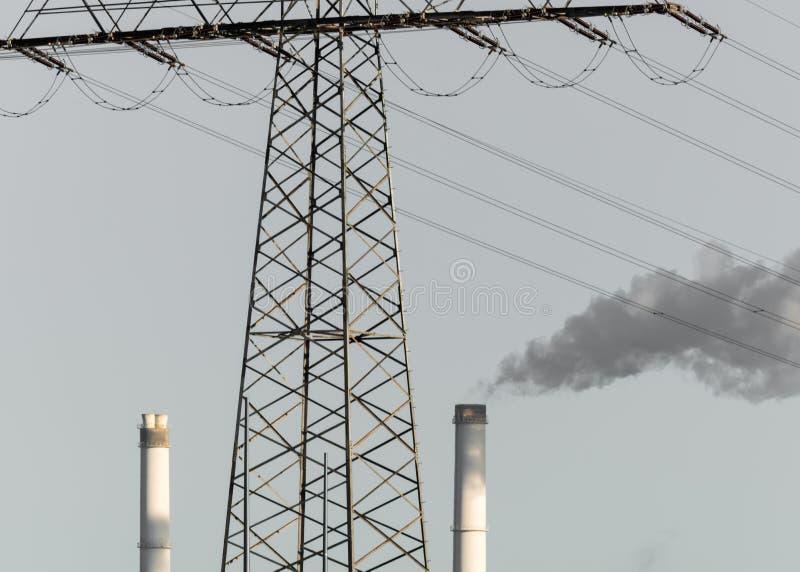 Πυλώνας ηλεκτρικού ρεύματος με δύο καμινάδες και καπνός από μία καμινάδα στοκ εικόνες