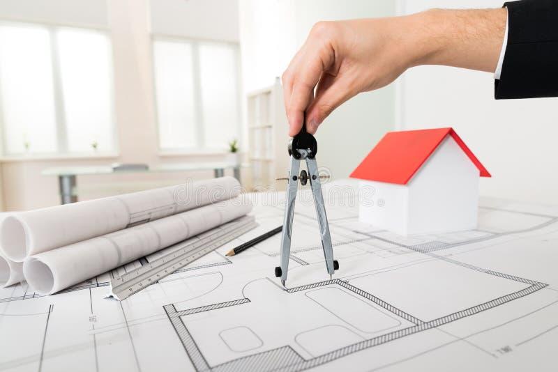 Πυξίδα εκμετάλλευσης χεριών αρχιτεκτόνων στο σχεδιάγραμμα στοκ φωτογραφία
