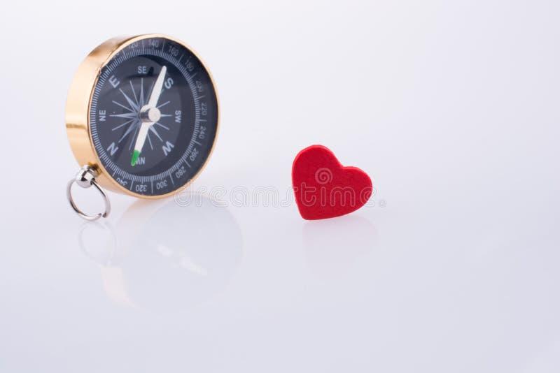 Πυξίδα κοντά σε μια κόκκινη καρδιά στοκ φωτογραφία