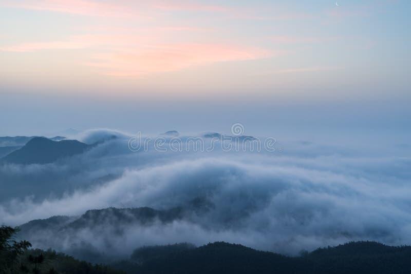 Πυράκτωση πρωινού και ομίχλη σύννεφων στα βουνά στοκ εικόνες